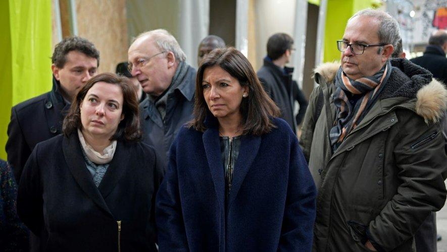 La maire de Paris Anne Hidalgo (C) et la ministre du Logement Emmanuelle Cosse (G) visitent un centre pour migrants à Paris le 8 novembre 2016