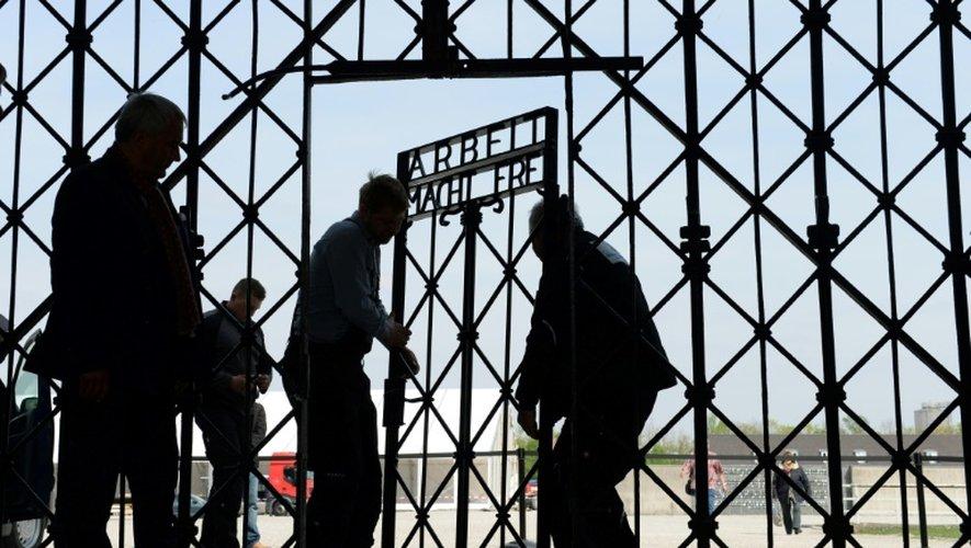 """Des ouvriers fixent la réplique du portail portant l'inscription """"Arbeit macht frei"""" de l'ancien camp de concentration à Dachau, dans le sud de l'Allemagne, le 29 avril 2015"""