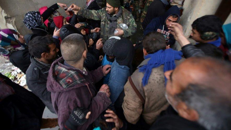 Des syriens font la queue pour recevoir à manger devant un centre gouvernemental accueillant les déplacés du fief rebelle d'Alep-Est à Jibrine, le 1er décembre 2016