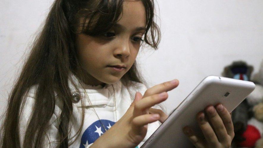La petite Syrienne Bana al-Abed regarde son compte Twitter sur un smartphone, le 12 octobre 2016 à Alep-est