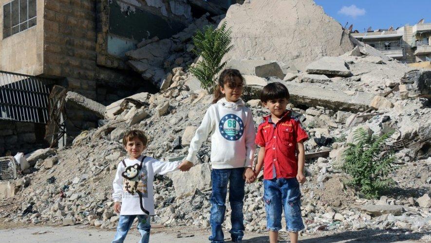 Bana (c) et ses frères devant des bâtiments détruits, le 10 octobre 2016 à Alep