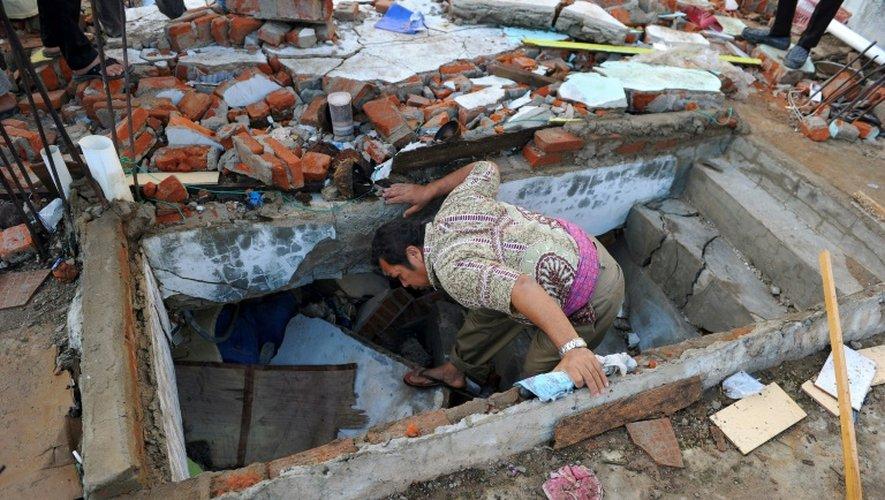 Un homme dont la femme et la fille ont été tuées dans le séisme, au milieu des décombres de son magasin le 8 décembre 2016 à Pidie Jaya dans la province d'Aceh