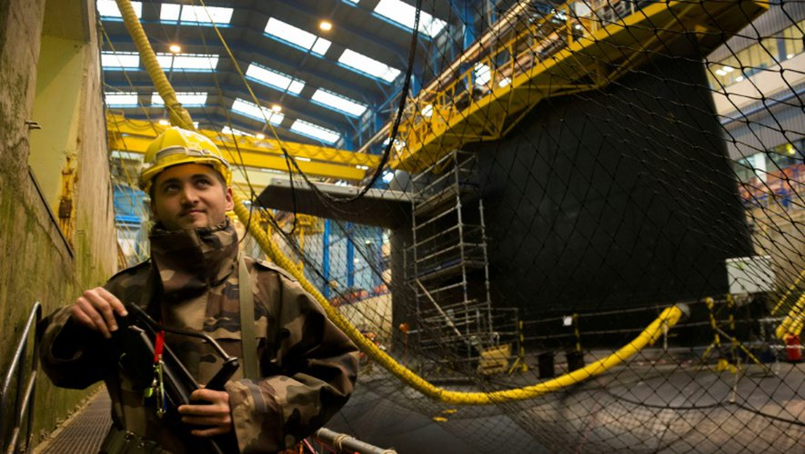 Un membre d'équipage d'un des quatre sous-marins lanceurs d'engins - SNLE- en cours de carénage dans une forme de radoub de la base de l'Île Longue dans la rade de Brest dans le Finistère, le 5 décembre 2016