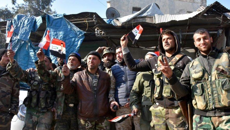 Des soldats du régime agitent des drapeaux syriens avec le portrait d'Assad dans le quartier de Bab al-Nairab à Alep le 10 décembre 2016