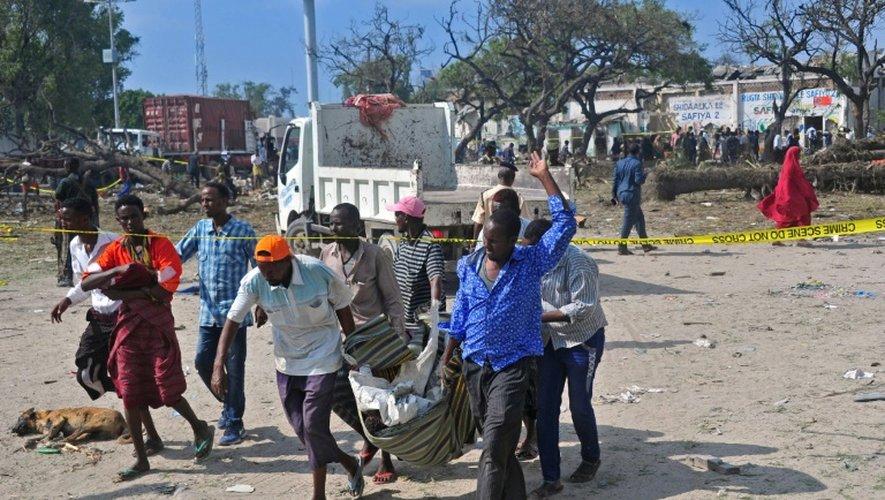 Des gens transportent le corps d'une victime de l'attentat-suicide au camion piégé qui a fait plus de 20 morts près de l'entrée du port de Mogadiscio