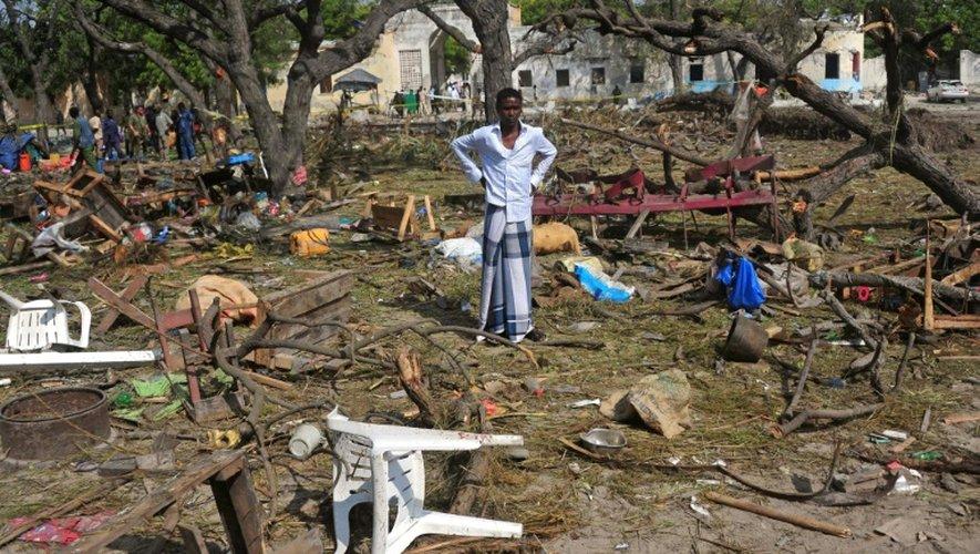 Le 11 décembre 2016 un homme se trouve au milieu d'objets épars sur les lieux de l'attentat-suicide au camion piégé près de l'entrée du port de Mogadiscio et qui a fait plus de 20 morts