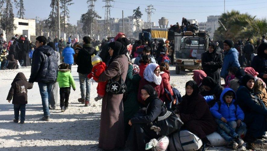 Des syriens attendent à un poste de contrôle d'Alep, le 10 décembre 2016 après avoir fui les quartiers Est de la ville