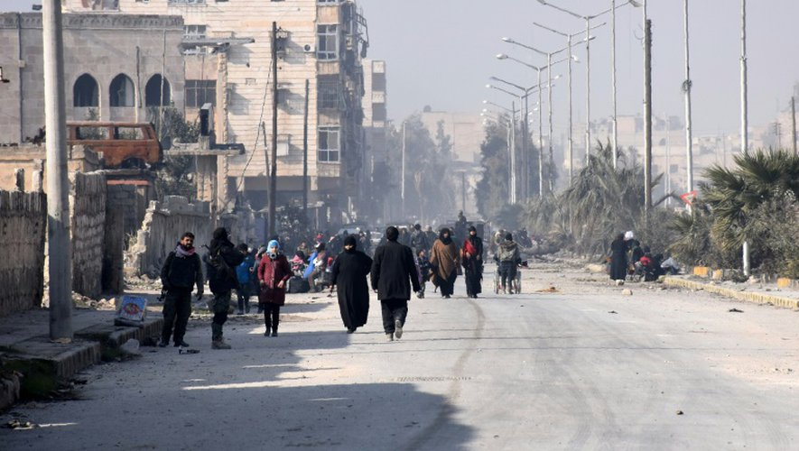 Des civils ayant quitté les quartiers est d'Alep se dirigent vers un poste de contrôle dans le centre de la ville, le 10 décembre 2016
