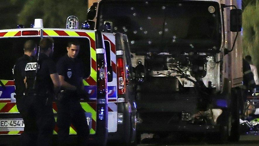 Des policiers devant le camion conduit par Mohamed Lahouaiej-Bouhlel, immobilisé après le carnage, au soir du 14 juillet 2016, sur la promenade des Anglais, à Nice