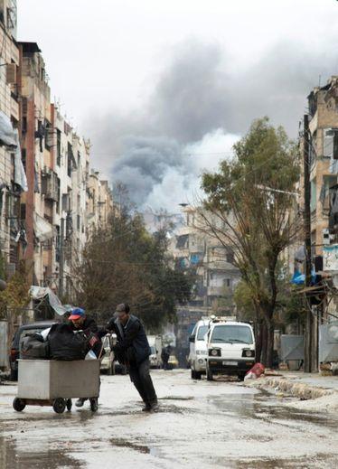Des syriens, le 14 décembre 2016, avec à l'arrière plan de la fumée sortant d'un quartier rebelle d'Alep