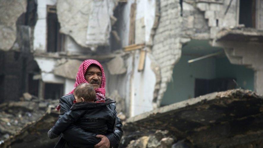 Un syrien quitte un quartier rebelle d'Alep avec son bébé le 13 décembre 2016 lors d'une opération menée par les forces gouvernementales syriennes pour reprendre la ville