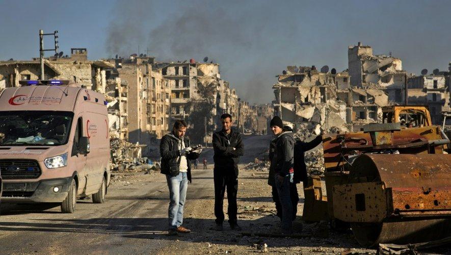 Des Syriens attendent dans le quartier d'al-Amiriyah pour être évacués vers des zones contrôlées par le régime à Ramoussa (sud d'Alep), le 15 décembre 2016