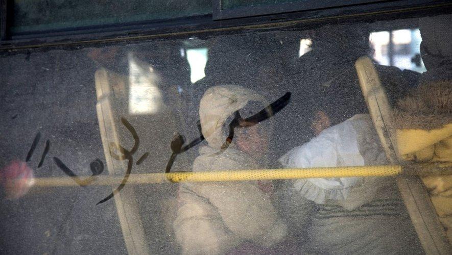 """""""Un jour nous reviendrons"""" est écrit sur la vitre d'un bus évacuant des civils d'Alep, le 15 décembre 2016"""