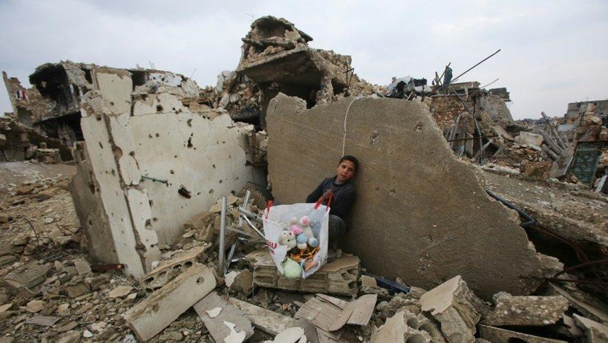 Un enfant avec quelques jouets récupérés dans les décombres de sa maison le 17 décembre 2016 à rubble of his house in Aleppo's Al-Arkoub dans la banlieue d'Alep