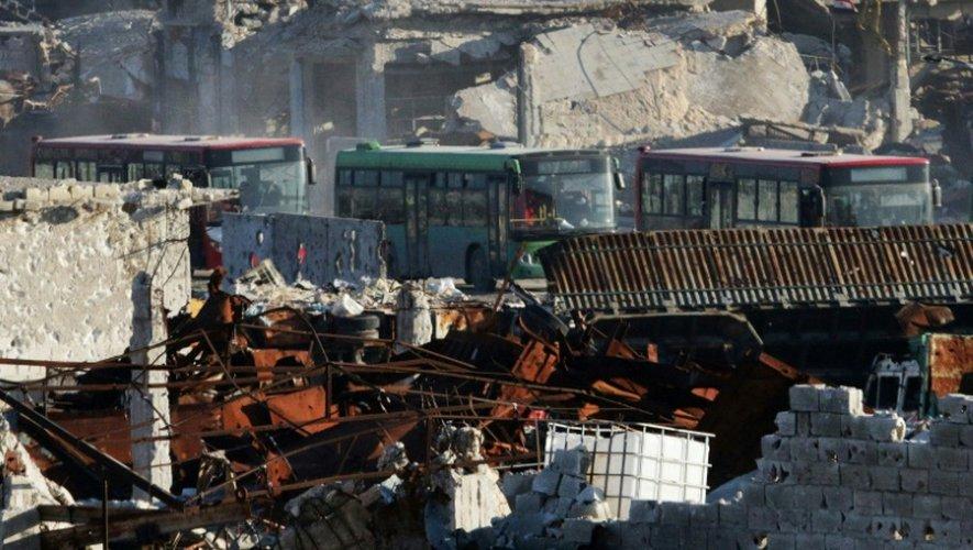 Des bus traversent  Ramoussa le 18 décembre 2016 dans la banlieue sud d'Alep