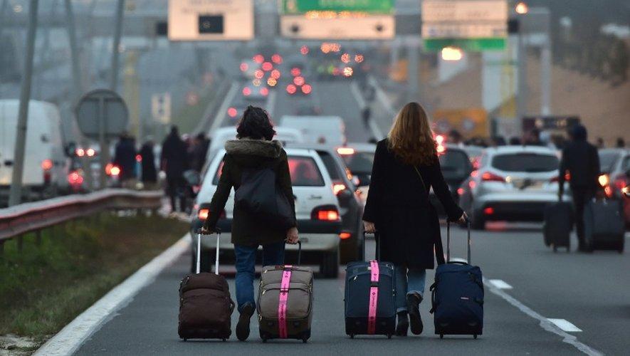 Des personnes marchent sur l'autoroute avec leurs bagages vers l'aéroport d'Orly, près de Paris, en raison d'un blocage routier des chauffeurs de VTC, le 17 décembre 2016