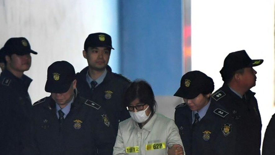 Le visage caché par un masque chirurgical et des lunettes à monture noire, Choi Soon-Sil à son arrivée le 19 décembre 2016 au tribunal à Seoul