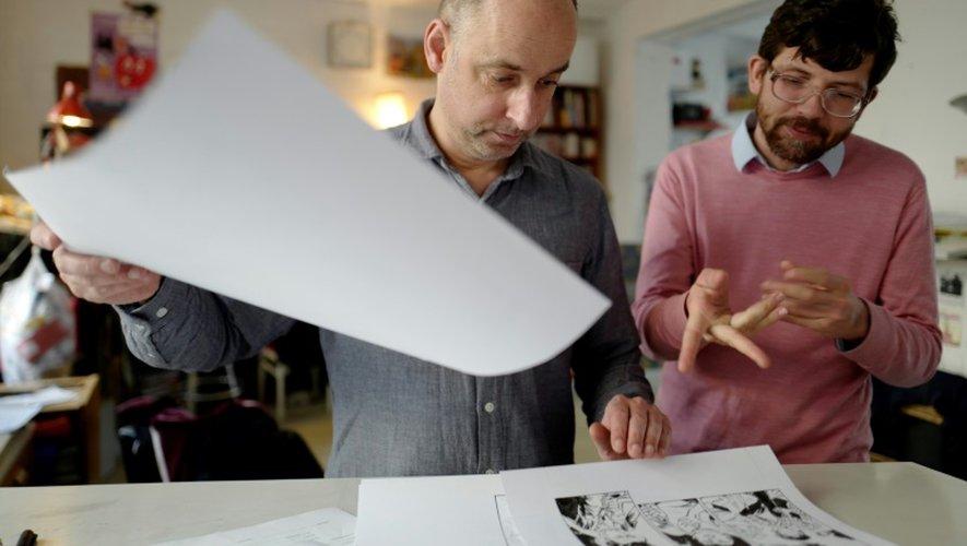 Le dessinateur Mawil (à droite) examine les planches de son collègue Reinhard Kleist (à gauche) dans leur studio à Berlin, le 23 novembre 2016
