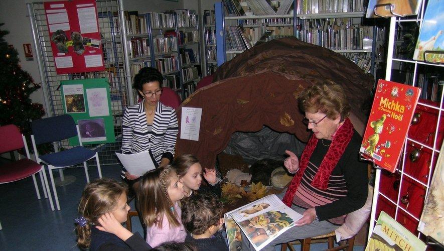 Devant la caverne où hiberne une famille ours, Zina lit un premier conte, sous le regard attentif des enfants.