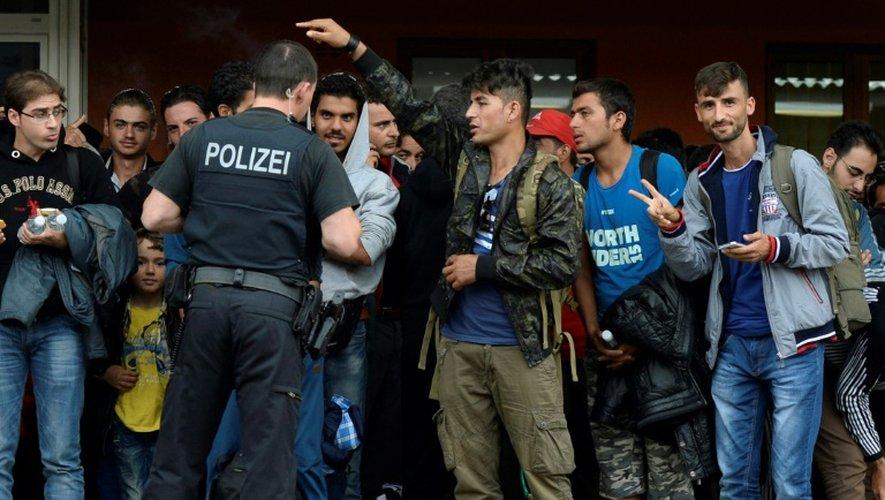Des migrants embarquent dans un train à la gare de Freilassing, à la frontière entre l'Autriche et l'Allemagne le 15 septembre 2015