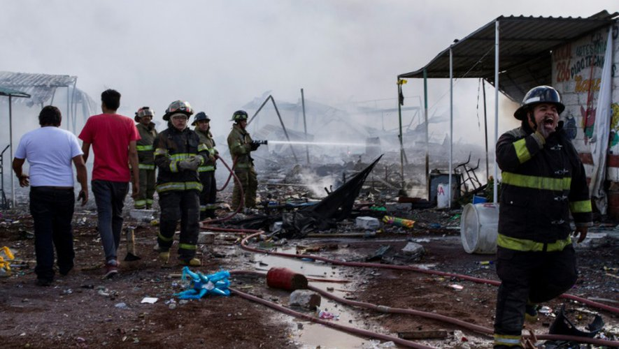 Des pompiers au milieu des décombres calcinés après l'explosion survenue le 20 décembre 2017 sur un marché de feux d'artifice à Tultepec, près de Mexico