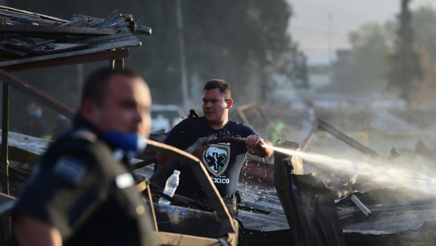 Des sauveteurs au milieu des décombres calcinés après l'explosion survenue le 20 décembre 2017 sur un marché de feux d'artifice à Tultepec, près de Mexico