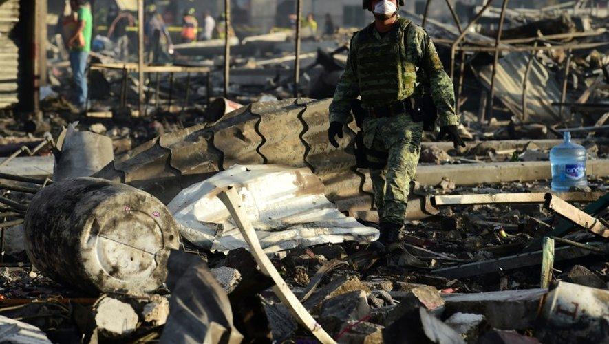Un homme au milieu des débris calcinés après l'explosion survenue sur un marché de feux d'artifice, le 20 décembre 2016 à Tupaltec près de Mexico