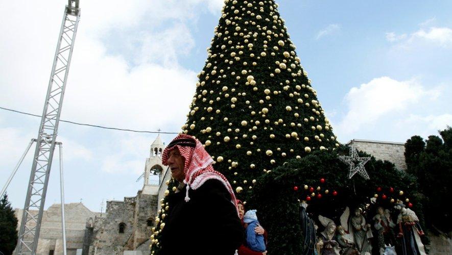 Un Palestinien le 20 décembre 2016 près d'un sapin de Noël géant place de la Mangeoire, à côté de l'Eglise de la Nativité, à Béthléem, lieu de naissance du Christ selon la Bible