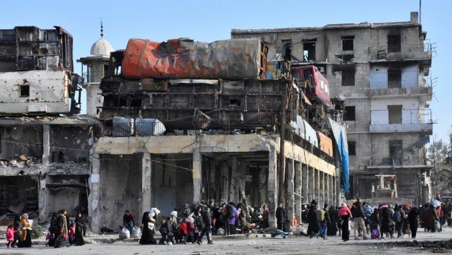 Des civils de dans un quartier repris par les forces pro-gouvernementales aux rebelles, le 8 décembre 2016 à Alep