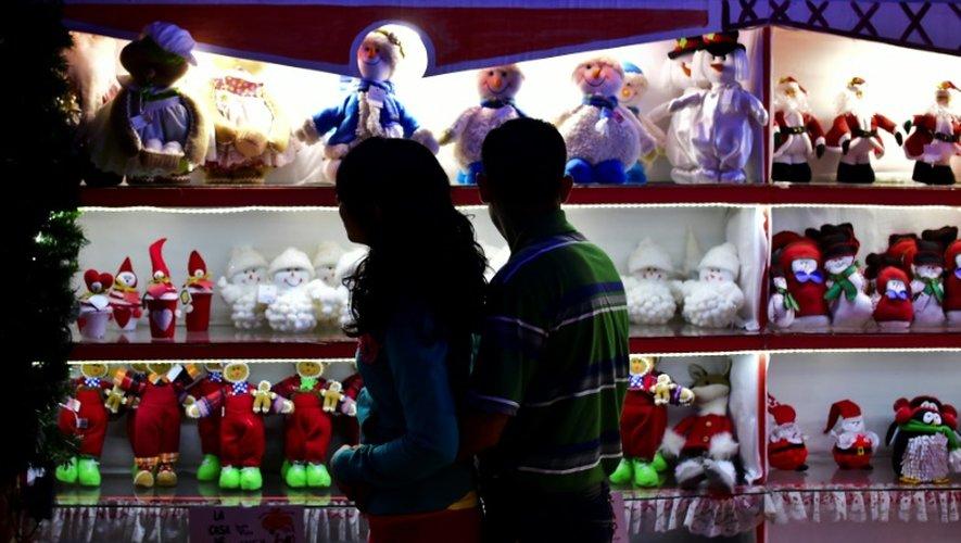 Des passants regardent des décorations de Noël dans une boutique à Tlalpujahua, dans l'Etat du Michoacan, le 16 décembre 2016 au Mexique