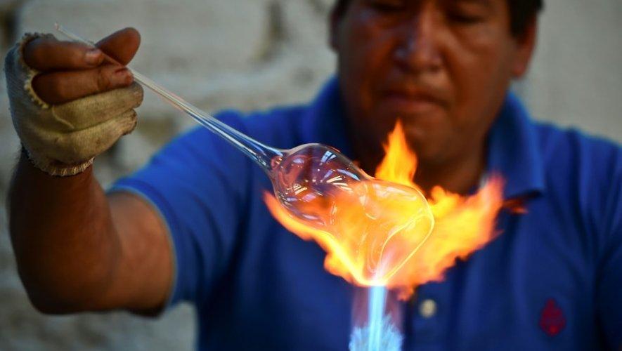 Un employé souffleur de verre réalise une boule de Noël dans une usine de Tlalpujahua, le 16 décembre 2016 dans l'Etat du Michoacan, au Mexique