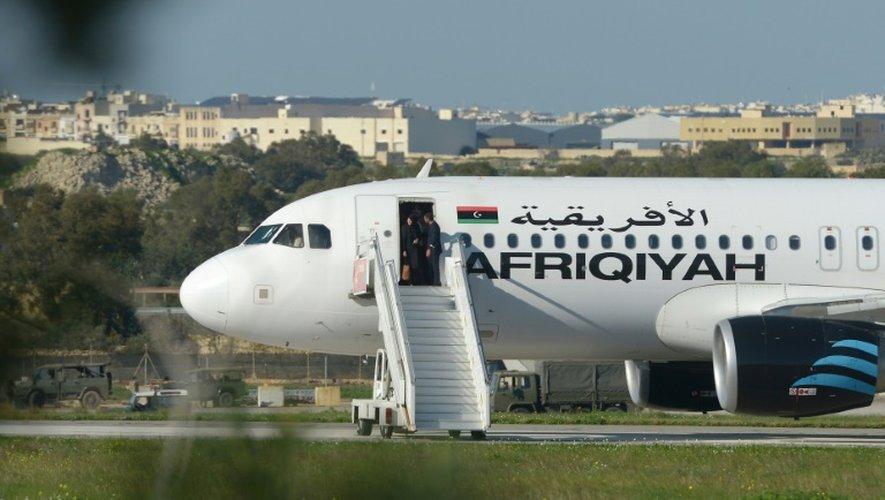 L'équipage aide des passagers à sortir de l'avion Afriqiyah Airways qui a été détourné sur Malte, le 23 décembre 2016