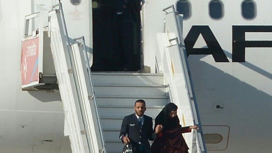 Un membre d'équipage descend de l'avion détourné avec un des otages, à l'aéroport de La Valette à Malte, le 23 décembre 2016