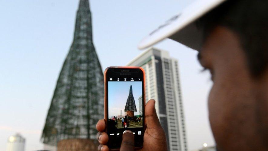 Un passant prend en photo l'arbre de Noël à Colombo, au Ski Lanka, présenté comme le plus haut au monde, le 24 décembre 2016
