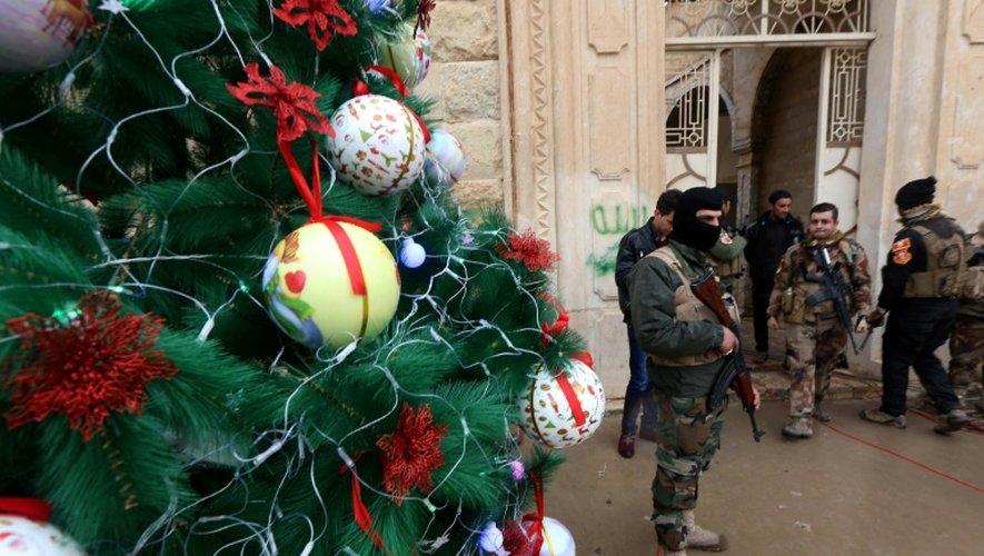 Des forces de sécurité irakiennes devant une église où des chrétiens s'apprêtent à assister à un office à Bartalla, près de Mossoul, le 24 décembre 2016