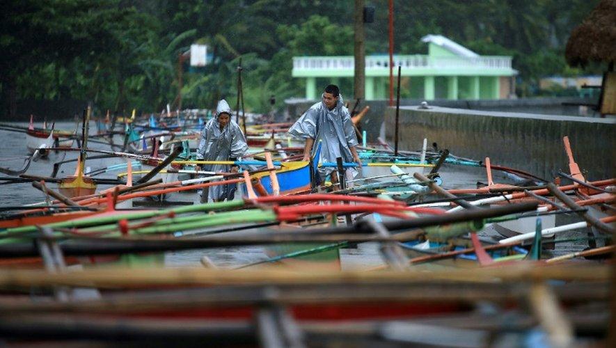Des pêcheurs vérifient les amarres de leurs bateaux dans la baie de Santo Domingo à l'approche du typhon Nock-Ten, le 25 décembre 2016 aux Philippines