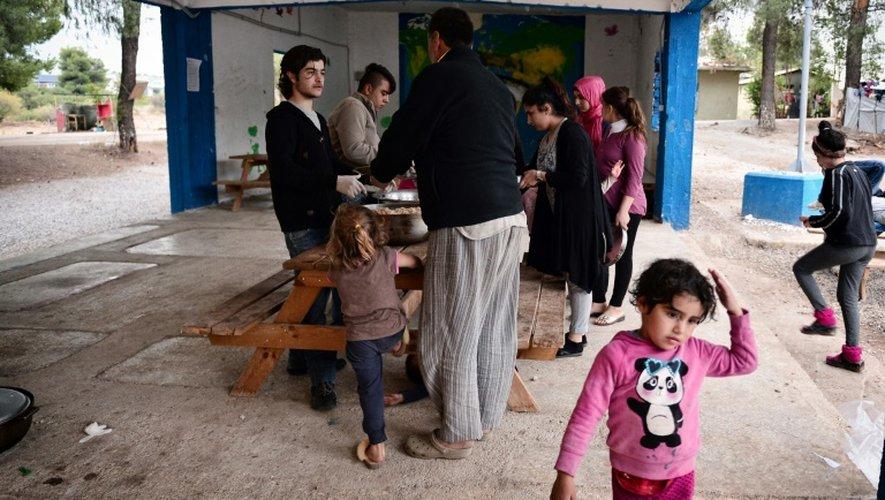 Des réfugiés du camp de Ritsona, au nord d'Athènes, reçoivent un repas préparé par le chef cuisinier syrien Talal Rankoussi, le 21 décembre 2016 en Grèce