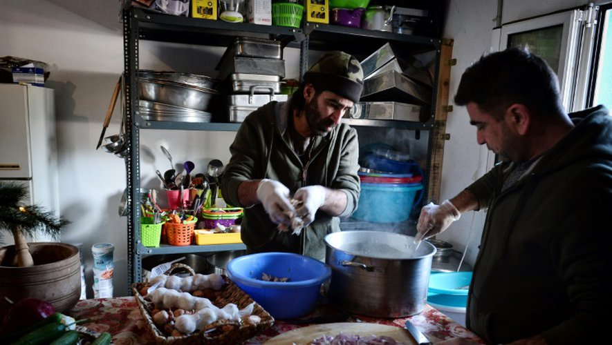 Le chef cuisinier syrien Talal Rankoussi (c) prépare un repas pour les réfugiés du camp de Ritsona, au nord d'Athènes, le 21 décembre 2016 en Grèce
