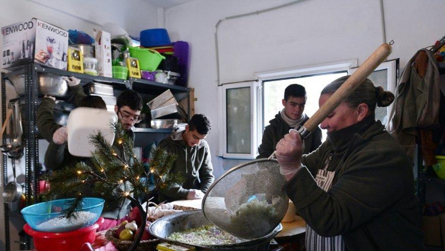 Carolynn Rockafellow (d) et des bénévoles aident le chef cuisinier Talal Rankoussi à préparer un repas pour les réfugiés du camp de Ritsona, au nord d'Athènes, le 21 décembre 2016 en Grèce