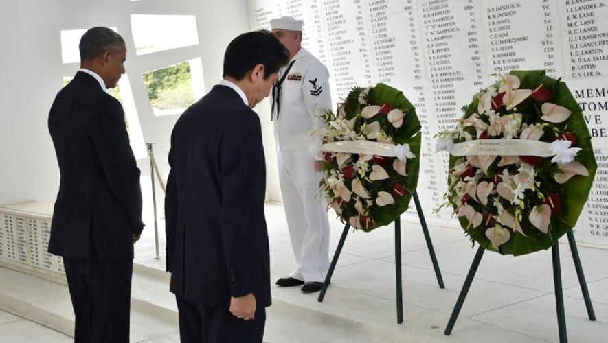Le Premier ministre japonais Shinzo Abe (g) et le président américain Barack Obama ont déposé des couronnes de fleurs le 27 décembre 2016 devant le mur sur lequel sont inscrits les noms des 1.177 victimes de Pearl Harbor, sur l'archipel d'Hawaï