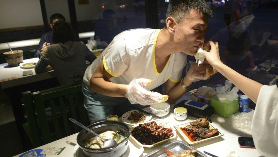 Un homme en train de manger une tête de lapin le 8 septembre 2016 dans un restaurant de Chengdu en Chine