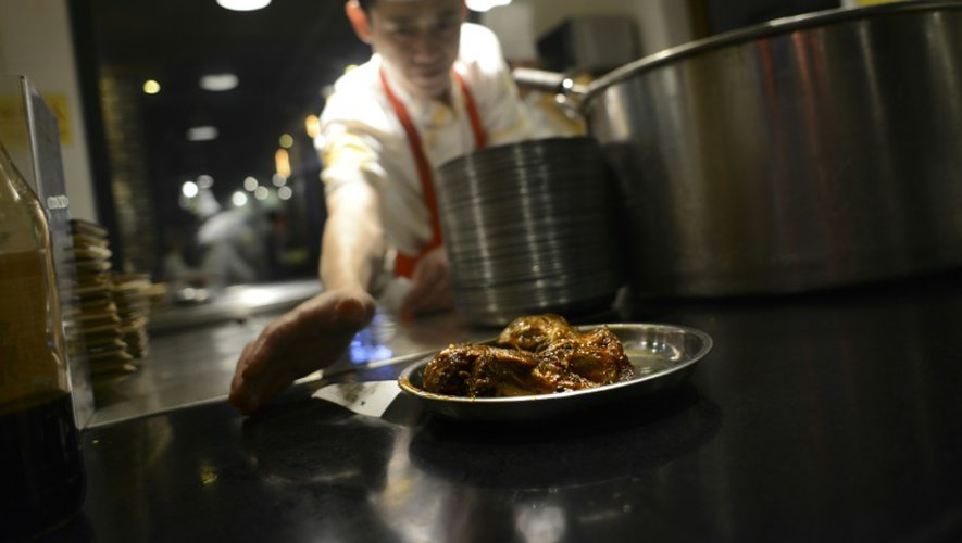 Un cuisinier sert des têtes de lapin le 8 septembre 2016 dans un restaurant de Chengdu en Chine
