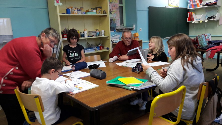 Brigitte et Yves attentifs aux devoirs de ce petit groupe d'écoliers