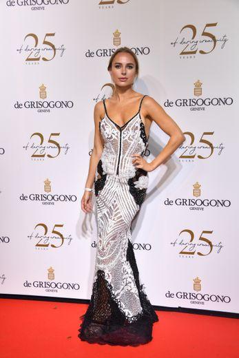 La designer Kimberley Garber a opté pour une longue robe à fines bretelles, entièrement recouvertes d'ornements scintillants et ouverte dans le dos pour fouler le tapis rouge de la soirée De Grisogono. Cannes, le 15 mai 2018.