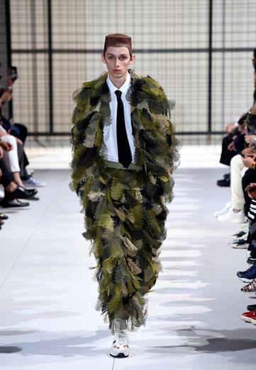 Comme des Garçons réinterprète totalement le costume avec des jeux de volume, créant un effet camo très moderne. Paris, le 22 juin 2018.