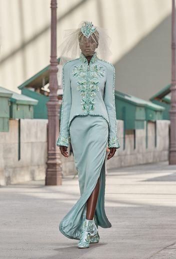 La maison Chanel se distingue avec une robe de mariée droite, légèrement fendue, en tweed vert pâle. Le tout accompagné d'une veste type redingote rebrodée de feuilles.