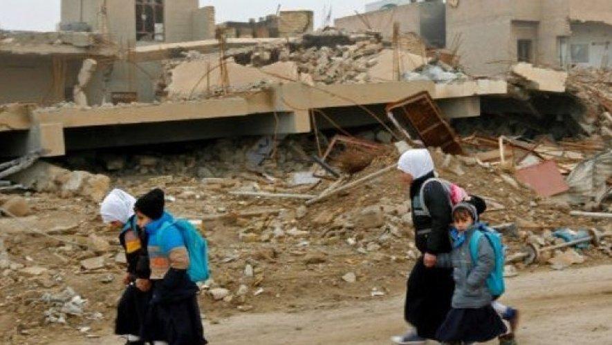 Des enfants irakiens marchent dans un quartier en ruines à Fallouja, en Irak, le 29 décembre 2016.