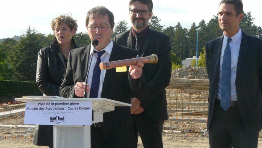 Le maire, avec le préfet et les élus départementaux, montrant le parchemin de la première pierre.