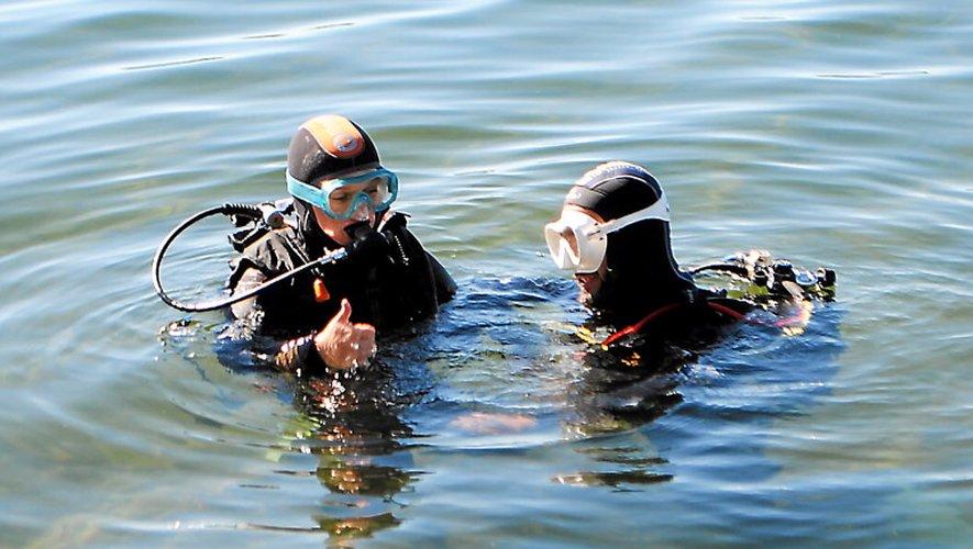 La communication sous l'eau se fait en quelques gestes simples que les plongeurs révisent avant d'explorer le lac.
