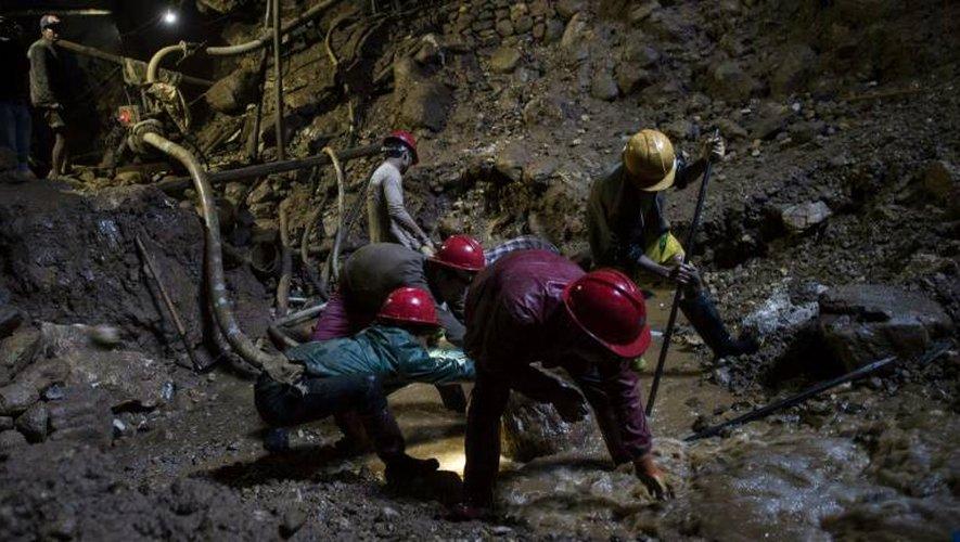 Des mineurs fouillent la terre dans une mine de rubis à Mogok, au nord de Mandalay, le 24 novembre 2016